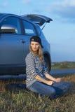 Mujer rubia joven con su coche quebrado Imagen de archivo