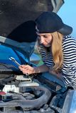 Mujer rubia joven con su coche quebrado Fotografía de archivo libre de regalías