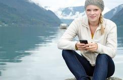 Mujer rubia joven con su Smartphone en la mano Imagen de archivo libre de regalías