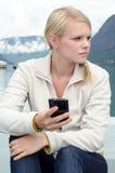 Mujer rubia joven con su Smartphone en la mano Fotos de archivo libres de regalías