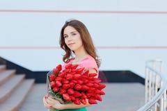 Mujer rubia joven con un ramo de tulipanes rojos Fotografía de archivo