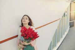 Mujer rubia joven con un ramo de tulipanes rojos Fotos de archivo libres de regalías