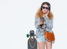 Mujer rubia joven de moda hermosa con un longboard, taza de café y auriculares frescos hablando en el teléfono Fotografía de archivo