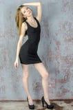 Mujer rubia joven de pelo largo hermosa con una figura delgada en un mini vestido negro Fotografía de archivo libre de regalías