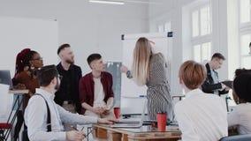 Mujer rubia joven del jefe que explica el diagrama del flipchart al equipo de los empleados en la EPOPEYA ROJA moderna de la cáma almacen de video