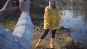 Mujer rubia joven del retrato que presenta cerca de bosque con el lago Hombre que hace la foto de su tel?fono cerca de m?vil metrajes