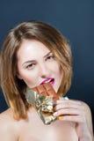 Mujer rubia joven desnuda hermosa con maquillaje brillante que come la barra de chocolate Fotografía de archivo libre de regalías