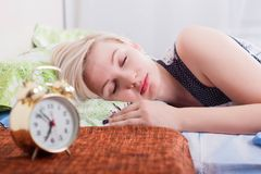 mujer rubia joven durmiente en dormitorio brillante en casa, mañana El reloj borroso en frente imagen de archivo