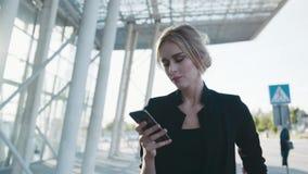 Mujer rubia joven elegante magnífica en un equipo formal que pasa el centro de negocio y que usa su teléfono, miradas alrededor