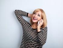Mujer rubia joven emocional feliz que habla en el teléfono móvil y el lo Fotografía de archivo