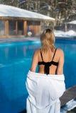 Mujer rubia joven en albornoz cerca de la piscina al aire libre en el invierno Foto de archivo libre de regalías