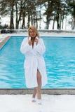 Mujer rubia joven en albornoz cerca de la piscina al aire libre en el invierno Fotografía de archivo libre de regalías