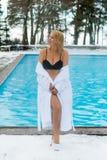 Mujer rubia joven en albornoz cerca de la piscina al aire libre en el invierno Imagenes de archivo
