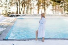 Mujer rubia joven en albornoz cerca de la piscina al aire libre en el invierno Fotos de archivo