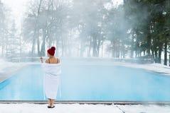Mujer rubia joven en albornoz y choza roja cerca de la piscina al aire libre en el invierno Fotos de archivo libres de regalías