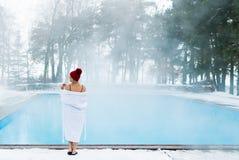 Mujer rubia joven en albornoz y choza roja cerca de la piscina al aire libre en el invierno Foto de archivo