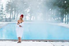 Mujer rubia joven en albornoz y choza roja cerca de la piscina al aire libre en el invierno Fotografía de archivo libre de regalías