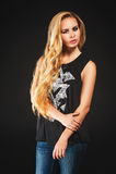 Mujer rubia joven en camiseta negra y vaqueros Fotografía de archivo