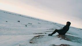 Mujer rubia joven en chaqueta negra y el casquillo que se sientan en orilla del mar congelado metrajes