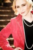 Mujer rubia joven en chaqueta roja Foto de archivo