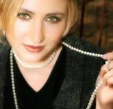 Mujer rubia joven en chaqueta y perlas grises de las lanas Imagen de archivo libre de regalías