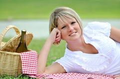 Mujer rubia joven en comida campestre con el vino Imagenes de archivo
