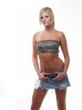 Mujer rubia joven en cortocircuitos hechos andrajos de los pantalones vaqueros Fotos de archivo libres de regalías