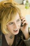 Mujer rubia joven en cuestión en el teléfono móvil Fotografía de archivo