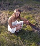 Mujer rubia joven en Dresss blanco en campo imagenes de archivo