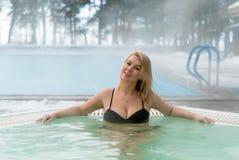 Mujer rubia joven en Jacuzzi de la bañera al aire libre en el invierno Imagen de archivo libre de regalías
