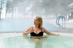 Mujer rubia joven en Jacuzzi de la bañera al aire libre en el invierno Imagenes de archivo