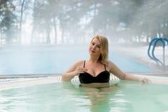 Mujer rubia joven en Jacuzzi de la bañera al aire libre en el invierno Foto de archivo libre de regalías
