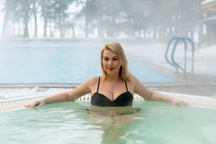 Mujer rubia joven en Jacuzzi de la bañera al aire libre en el invierno Fotos de archivo libres de regalías