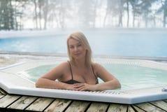 Mujer rubia joven en Jacuzzi de la bañera al aire libre en el invierno Fotografía de archivo libre de regalías