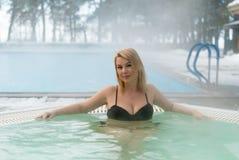 Mujer rubia joven en Jacuzzi de la bañera al aire libre en el invierno Fotos de archivo