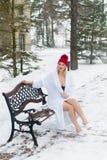 Mujer rubia joven en la albornoz y la choza roja que se sientan en banco en el invierno al aire libre Fotos de archivo
