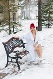 Mujer rubia joven en la albornoz y la choza roja que se sientan en banco en el invierno al aire libre Imagenes de archivo