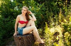 Mujer rubia joven en la naturaleza, sentándose en tocón Fotografía de archivo libre de regalías