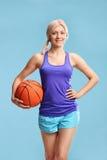 Mujer rubia joven en la ropa de deportes que lleva a cabo un baloncesto Imagen de archivo libre de regalías