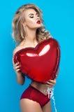 Mujer rubia joven en lencería sexy con el globo del corazón Fotografía de archivo libre de regalías