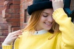 Mujer rubia joven en sombrero negro y suéter amarillo Imagenes de archivo