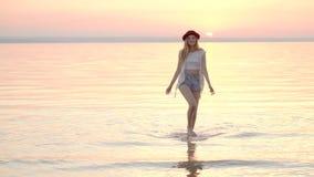Mujer rubia joven en sombrero que disfruta de vacaciones de verano en la puesta del sol de oro del océano almacen de metraje de vídeo
