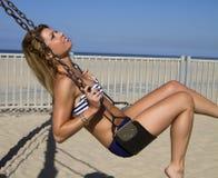 Mujer rubia joven en un oscilación en la playa Fotografía de archivo libre de regalías