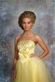Mujer rubia joven en un vestido amarillo elegante Fotos de archivo