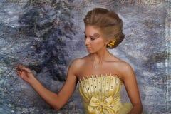 Mujer rubia joven en un vestido amarillo elegante Fotografía de archivo