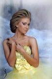 Mujer rubia joven en un vestido amarillo elegante Imagenes de archivo