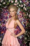 Mujer rubia joven en un vestido rosado elegante Imagen de archivo libre de regalías