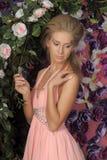 Mujer rubia joven en un vestido rosado elegante Imágenes de archivo libres de regalías