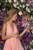 Mujer rubia joven en un vestido rosado elegante Foto de archivo