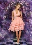 Mujer rubia joven en un vestido rosado elegante Fotografía de archivo